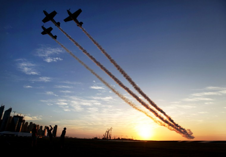 An aerobatics team roars overhead at sunset as those on the ground take pictures at the World Air Games in Dubai, United Arab Emirates, on Sunday, Dec. 6, 2015. The World Air Games includes precision aerobatics, skydiving and hot air balloon competitions. (AP Photo/Jon Gambrell)
