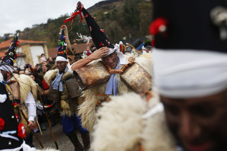 "Men dressed in sheepskins and jingling bells to make noise, and so called ""Zamarracos"", march during the Vijanera Festival, in the small village of Silio, northern Spain, Sunday, Jan. 3, 2016. The Vijanera masquerade, of pre-Roman origin, is the first carnival of the year in Europe symbolizing the triumph of good over evil and involving the participation of crowds of residents wearing different masks, animal skins and brightly coloured clothing with its own complex function and symbolism and becoming the living example of the survival of archaic cults to nature. (AP Photo/Francisco Seco)"