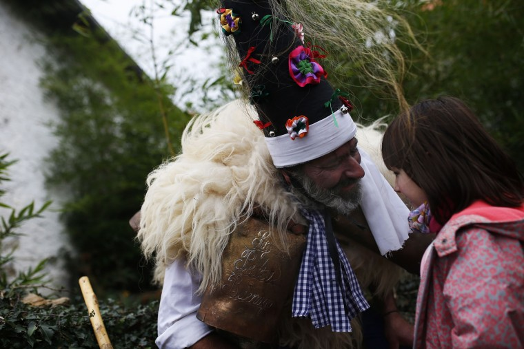 "A man, so called ""Zamarraco,"" dressed in sheepskins and bells to make noise, talks to a young girl during the Vijanera Festival, in the small village of Silio, northern Spain, Sunday, Jan. 3, 2016. The Vijanera masquerade, of pre-Roman origin, is the first carnival of the year in Europe symbolizing the triumph of good over evil and involving the participation of crowds of residents wearing different masks, animal skins and brightly coloured clothing with its own complex function and symbolism and becoming the living example of the survival of archaic cults to nature. (AP Photo/Francisco Seco)"
