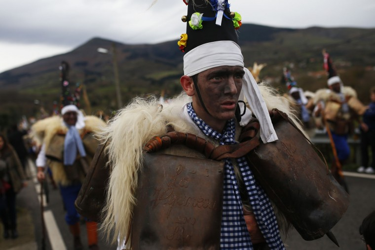 "A man, so called ""Zamarraco,"" dressed in sheepskins and bells to make noise, marches with others during the Vijanera Festival, in the small village of Silio, northern Spain, Sunday, Jan. 3, 2016. The Vijanera masquerade, of pre-Roman origin, is the first carnival of the year in Europe symbolizing the triumph of good over evil and involving the participation of crowds of residents wearing different masks, animal skins and brightly coloured clothing with its own complex function and symbolism and becoming the living example of the survival of archaic cults to nature. (AP Photo/Francisco Seco)"