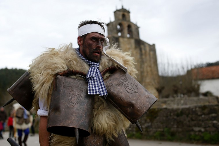 "A man, so called ""Zamarraco,"" dressed in sheepskins with jingling bells to make noise, marches with others during the Vijanera Festival, in the small village of Silio, northern Spain, Sunday, Jan. 3, 2016. The Vijanera masquerade, of pre-Roman origin, is the first carnival of the year in Europe symbolizing the triumph of good over evil and involving the participation of crowds of residents wearing different masks, animal skins and brightly coloured clothing with its own complex function and symbolism and becoming the living example of the survival of archaic cults to nature. (AP Photo/Francisco Seco)"