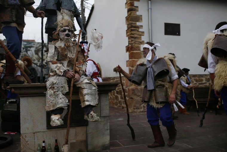 "A man, so called ""Zamarraco,"" right, dressed in sheepskins and jingling bells to make noise, dances next to another dressed as a ""Trapajon"", left, representing entities of nature, during the Vijanera Festival, in the small village of Silio, northern Spain, Sunday, Jan. 3, 2016. The Vijanera masquerade, of pre-Roman origin, is the first carnival of the year in Europe symbolizing the triumph of good over evil and involving the participation of crowds of residents wearing different masks, animal skins and brightly coloured clothing with its own complex function and symbolism and becoming the living example of the survival of archaic cults to nature. (AP Photo/Francisco Seco)"