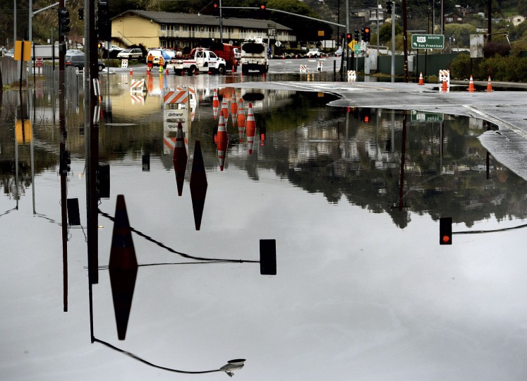 CalTrans personnel divert traffic around a flooded transit station caused by a high tide and rain Tuesday, Jan. 5, 2016, in Mill Valley, Calif. Californians were warned against abandoning conservation efforts Tuesday as several weeks of storms spawned by El Nino began hitting the West Coast. Heavy rain and snow are welcome after four years of drought in California, despite their potential for causing flash floods and mudslides. But even a very wet winter won't be enough to replenish water supplies depleted by four years of drought. (Robert Tong/Marin Independent Journal via AP)