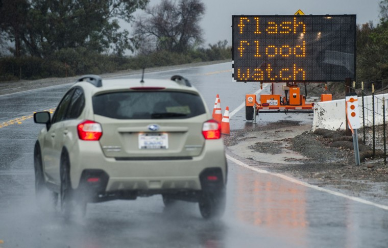 A sign on Silverado Canyon Road lets residents know that there is a flash flood watch in effect in Silverado Canyon Tuesday morning, Jan. 5, 2016, in Irvine, Calif., as the first storm of the season brought heavy rain to Orange County. Californians were warned against abandoning conservation efforts Tuesday as several weeks of storms spawned by El Nino began hitting the West Coast. Heavy rain and snow are welcome after four years of drought in California, despite their potential for causing flash floods and mudslides. (Mark Rightmire/The Orange County Register via AP)