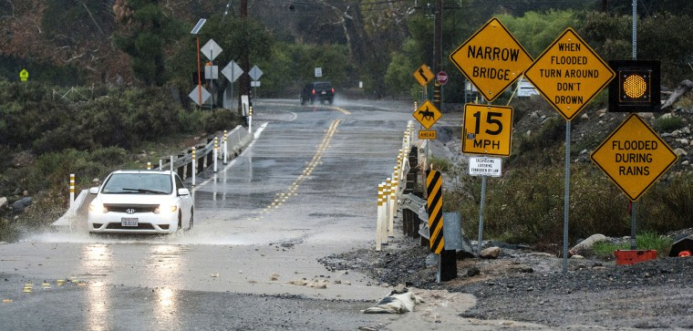A car makes its way carefully along Trabuco Canyon Road through runoff debris at Trabuco Creek Tuesday morning, Jan. 5, 2016, in Irvine, Calif., as the first storm of the season brought rain to Orange County. Californians were warned against abandoning conservation efforts Tuesday as several weeks of storms spawned by El Nino began hitting the West Coast. Heavy rain and snow are welcome after four years of drought in California, despite their potential for causing flash floods and mudslides. (Mark Rightmire/The Orange County Register via AP)