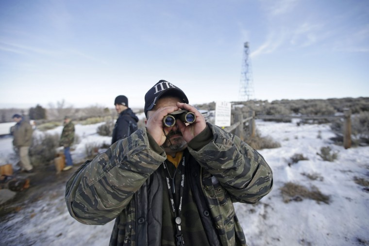Sean Anderson, of Idaho, a supporter of the group occupying the Malheur National Wildlife Refuge, looks through binoculars at the front gate Wednesday, Jan. 6, 2016, near Burns, Ore. With the takeover entering its fourth day Wednesday, authorities had not removed the group of roughly 20 people from the Malheur National Wildlife Refuge in eastern Oregon's high desert country. (AP Photo/Rick Bowmer)