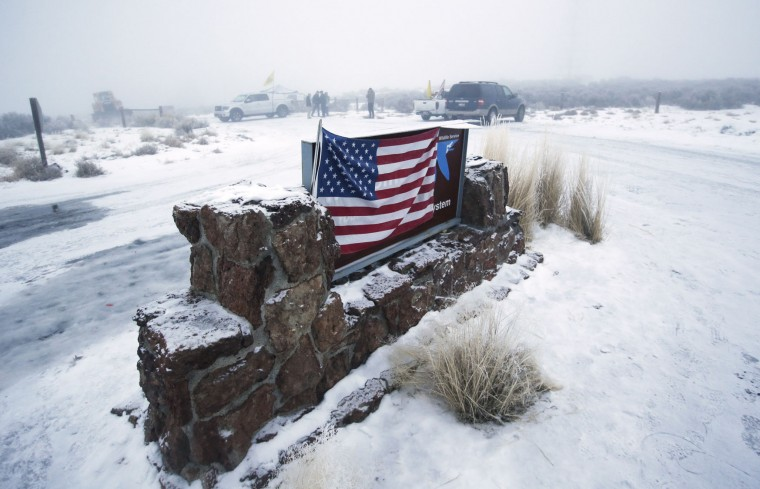 "An American flag hangs on the sign at the front entrance of the Malheur National Wildlife Refuge Thursday, Jan. 7, 2016, near Burns, Ore. Cheers erupted Wednesday evening at a packed community meeting in rural Oregon when a sheriff said it was time for a small, armed group occupying the national wildlife refuge to ""pick up and go home."" (AP Photo/Rick Bowmer)"