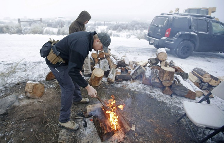 """A member of the group occupying the Malheur National Wildlife Refuge headquarters stands next to a fire Thursday, Jan. 7, 2016, near Burns, Ore. Cheers erupted Wednesday evening at a packed community meeting in rural Oregon when a sheriff said it was time for a small, armed group occupying the national wildlife refuge to """"pick up and go home."""" (AP Photo/Rick Bowmer)"""