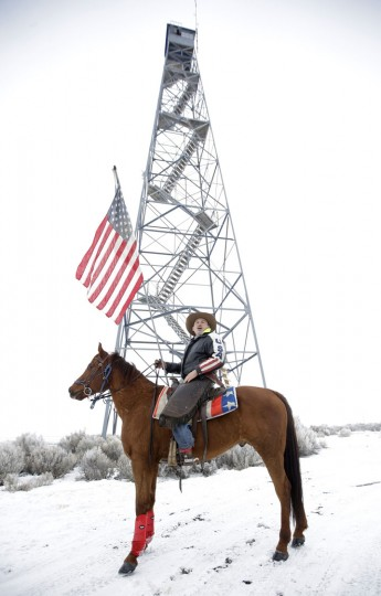 Cowboy Dwane Ehmer, of Irrigon Ore., a supporter of the group occupying the Malheur National Wildlife Refuge, holds a U.S. flag as he talks with a journalist next to a manned watch tower Thursday, Jan. 7, 2016, near Burns, Ore. A small, armed group occupying the wildlife preserve has said repeatedly that local people should control federal lands, but critics say the lands are already managed to help everyone from ranchers to recreationalists. (AP Photo/Rick Bowmer)