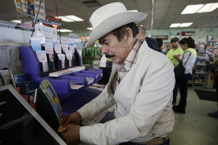 Fausto Aguilar checks lottery tickets from a previous drawing as he buys Powerball lottery tickets at Kavanagh Liquors Wednesday, Jan. 13, 2016, in San Lorenzo, Calif. The Powerball jackpot for Wednesday night's drawing is at least $1.5 billion, the largest lottery jackpot in the world. (AP Photo/Marcio Jose Sanchez)