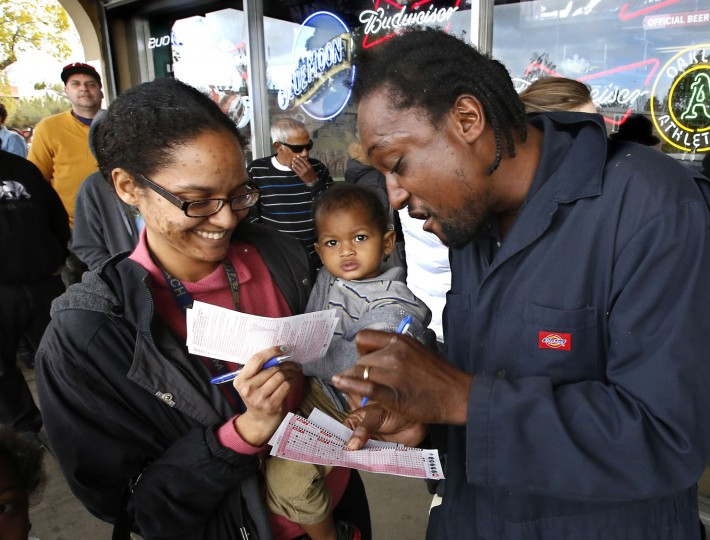 Nicole Madison holds her son, Jacob Madison, Jr, 1, as she and her husband, Jacob Madison, right, pick their Powerball numbers while waiting in line at Lichine's Liquor store, Wednesday, Jan. 13, 2016, in Sacramento, Calif. The Powerball jackpot for Wednesday night's drawing is estimated to be over $1 billion, the largest lottery jackpot in the world. (AP Photo/Rich Pedroncelli)
