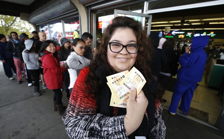 Laura Woodward displays the Powerball lottery tickets she bought for her office pool at Lichine's Liquor store, Wednesday, Jan. 13, 2016, in Sacramento, Calif. The Powerball jackpot for Wednesday night's drawing to be over $1 billion, the largest lottery jackpot in the world. (AP Photo/Rich Pedroncelli)