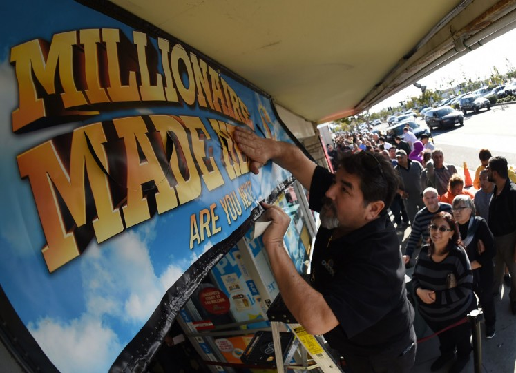 A lottery worker puts up a new promotional sign as people line up to buy California Powerball lottery tickets at the famous Bluebird Liquor store, considered to be a lucky retailer of tickets, in Hawthorne, California on January 13, 2016. Record sales drove up the largest jackpot in US history to a whopping $1.5 billion as people dreaming of riches flocked across state lines and international borders to buy tickets. (Mark Ralston/AFP/Getty Images)