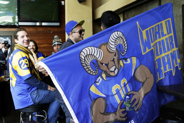 Rams fans celebrate the impending return of the NFL football team to Los Angeles, at Big Wangs sports bar in the North Hollywood area of Los Angeles on Wednesday, Jan. 13, 2016. League owners voted Tuesday to allow the St. Louis Rams to move to Los Angeles starting next season. (AP Photo/Nick Ut)