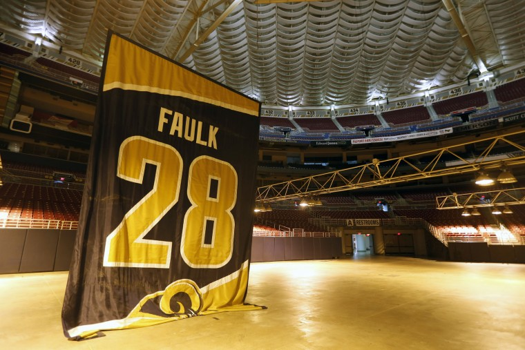 A banner honoring Rams great Marshall Faulk is removed from the ceiling of the ceiling of the Edward Jones Dome, former home of the St. Louis Rams football team, Thursday, Jan. 14, 2016, in St. Louis. The Rams will begin playing in Los Angeles starting with the 2016 season. (AP Photo/Jeff Roberson)