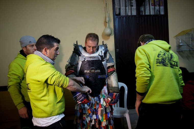 Stewards dress up Jarramplas Armando Vicente Vicente 30, before he makes his way through the streets beating his drum during the Jarramplas Festival on January 20, 2016 in Piornal, Caceres province, Spain. The centuries old Jarramplas festival takes place annually every January 19-20 on Saint Sebastian Day and this year they expect to use more than 20 thousand kilogrames of turnips. Even though the exact origins of the festival are not known, various theories exist including the mythological punishment of Caco by Hercules, a relation to ceremonies celebrated by the American Indians that were seen by the first conquerors, to a cattle thief ridiculed and expelled by his village neighbours. It is generally believed to symbolize the expulsion of everything bad. (Pablo Blazquez Dominguez/Getty Images)