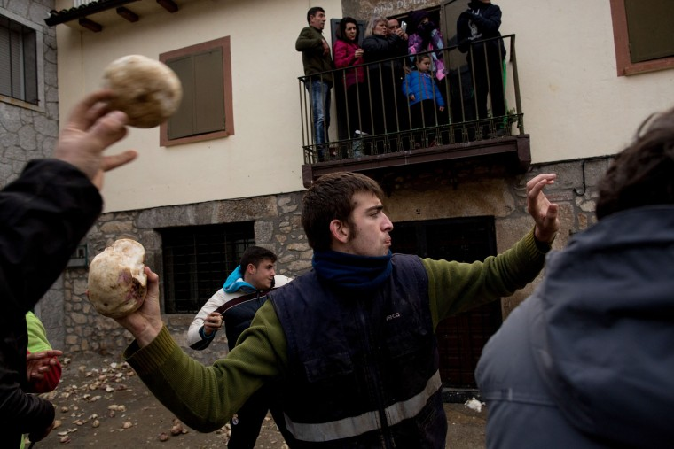People throw turnips at the Jarramplas (not in the picture) as he makes his way through the streets beating his drum during the Jarramplas Festival on January 20, 2016 in Piornal, Caceres province, Spain. The centuries old Jarramplas festival takes place annually every January 19-20 on Saint Sebastian Day and this year they expect to use more than 20 thousand kilogrames of turnips. Even though the exact origins of the festival are not known, various theories exist including the mythological punishment of Caco by Hercules, a relation to ceremonies celebrated by the American Indians that were seen by the first conquerors, to a cattle thief ridiculed and expelled by his village neighbours. It is generally believed to symbolize the expulsion of everything bad. (Pablo Blazquez Dominguez/Getty Images)