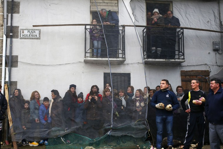 People take shelter behind a net as they wait for the Jarramplas to make his way through the streets beating his drum during the Jarramplas festival in Piornal, Spain, Wednesday, Jan. 20, 2016. Hundreds of people are running through the streets of a tiny town in southwestern Spain, chasing a fancy-dressed, beast-like figure and pelting it with turnips. (AP Photo/Francisco Seco)