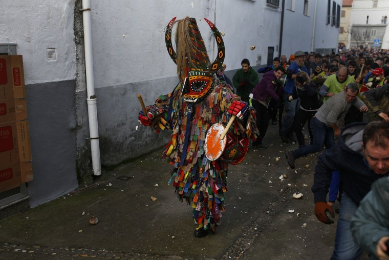 People throw turnips at the Jarramplas as he makes his way through the streets beating his drum during the Jarramplas festival in Piornal, Spain, Wednesday, Jan. 20, 2016. Hundreds of people are running through the streets of a tiny town in southwestern Spain, chasing a fancy-dressed, beast-like figure and pelting it with turnips. (AP Photo/Francisco Seco)