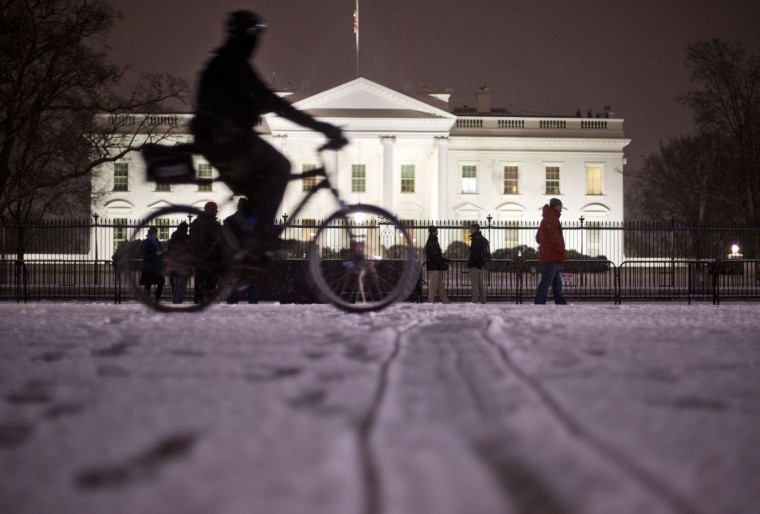 A bicyclist rides past the White House during evening snowfall in Washington, Wednesday, Jan. 20, 2016. As Washington prepares for this weekend's snowstorm, now forecast to reach blizzard conditions, a small clipper system pushed through the region Wednesday night causing massive delays and issues on the roads.(AP Photo/Pablo Martinez Monsivais)