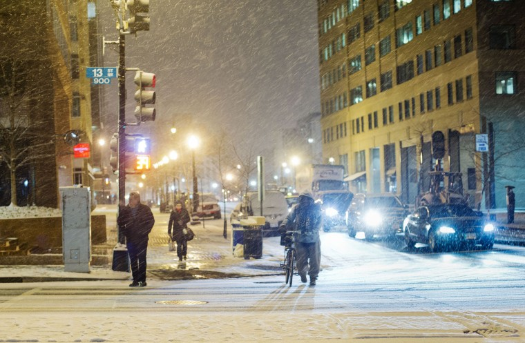 Pedestrian wait to cross 13th street in downtown Washington during an evening snowfall, Wednesday, Jan. 20, 2016. As Washington prepares for this weekend's snowstorm, now forecast to reach blizzard conditions, a small clipper system pushed through the region Wednesday night causing massive delays and issues on the roads.(AP Photo/Pablo Martinez Monsivais)