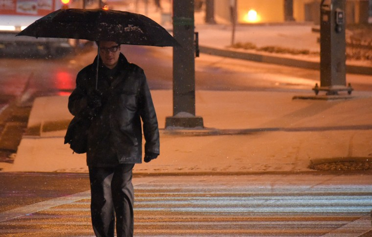 David Paster of Baltimore walks up Pratt Street, toward a hotel to meet a friend while light snow falls in downtown Baltimore, a precursor to a forecasted potential blizzard that is expected in less than two days. (Karl Merton Ferron/Baltimore Sun)