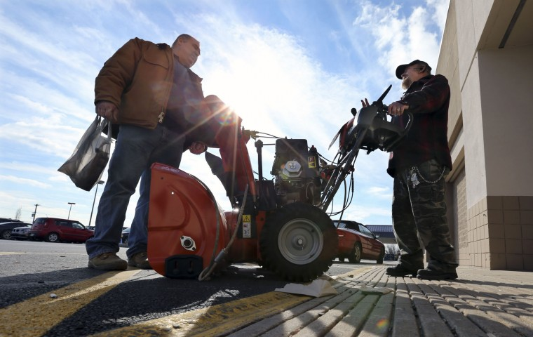 Richard Warner, of Newtown, Pa., right, and an unidentified man discuss the pros and cons of various snowblowers outside a Lowe's home improvement warehouse Thursday, Jan. 21, 2016, in Langhorne, Pa. The northern mid-Atlantic region, including Baltimore, Washington and Philadelphia, is preparing for a weekend snowstorm that is now forecast to reach blizzard conditions. (AP Photo/Mel Evans)