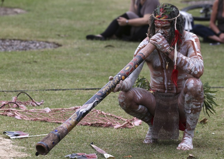 An Aboriginal man plays a didgeridoo during Australia Day in Sydney, Australia, Tuesday, Jan. 26, 2016. Australia Day is the anniversary of the arrival and landing of the First Fleet of convict ships from Great Britain, and the raising of the Union Jack at Sydney Cove by Captain Arthur Phillip, on Jan 26, 1788. (AP Photo/Rob Griffith)