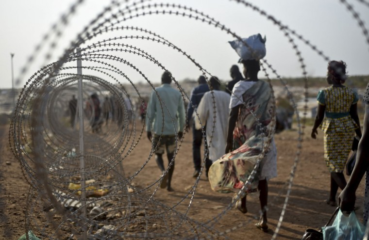 In this photo taken Tuesday, Jan. 19, 2016, displaced people walk next to a razor wire fence at the United Nations base in the capital Juba, South Sudan. When a delegation of South Sudanese rebels returned to the government-controlled capital Juba last month after two years of war, many refugees thought they would finally return to the homes they fled. But prospects for peace seem dim after the government and rebels missed a deadline last week to form a power-sharing government and end the war. President Salva Kiir, an ethnic Dinka, and rebel leader Riek Machar, a Nuer, signed a peace deal in August, but fighting continues. Machar said Tuesday, Jan. 26 in Kampala, Uganda that he won't return to Juba, South Sudan's capital, because the decree violated the peace accord. (AP Photo/Jason Patinkin)
