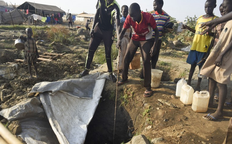 In this photo taken Tuesday, Jan. 19, 2016, displaced people draw water from a hole dug in the ground, in the United Nations camp for displaced people in the capital Juba, South Sudan. When a delegation of South Sudanese rebels returned to the government-controlled capital Juba last month after two years of war, many refugees thought they would finally return to the homes they fled. But prospects for peace seem dim after the government and rebels missed a deadline last week to form a power-sharing government and end the war. (AP Photo/Jason Patinkin)
