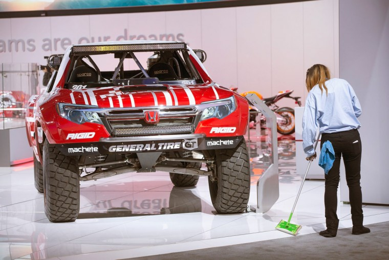 A worker cleans up around a Honda Ridgeline race truck on display at the North American International Auto Show on January 12, 2016 in Detroit, Michigan. The show is open to the public from January 16-24. (Photo by Scott Olson/Getty Images)