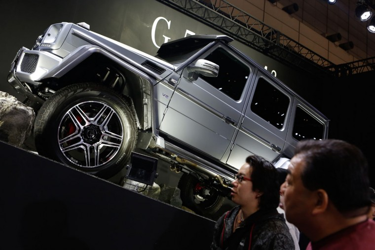 Visitors look at a Mercedes-Benz G550 4x4 Squared vehicle on display at the 2016 Tokyo Auto Salon car show on January 15, 2016 in Chiba, Japan. (Photo by Christopher Jue/Getty Images)