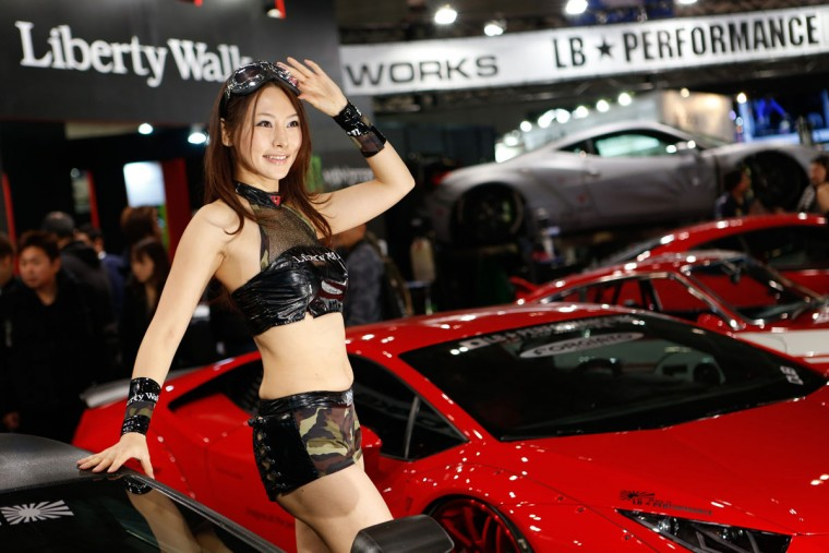 A campaign model (R) poses for visitors during the 2016 Tokyo Auto Salon car show on January 15, 2016 in Chiba, Japan. TOKYO AUTO SALON 2016 is held from January 15 to 17, 2016. (Photo by Christopher Jue/Getty Images)