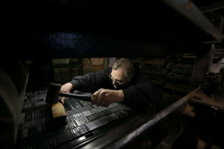 Saguache Crescent owner and editor Dean Coombs uses a mallet to even out a plate of metal type text before printing the Saguache Crescent newspaper on January 19, 2016 in Saguache, Colorado. The Saguache Crescent newspaper is the last newspaper in the United States that is produced using a Linotype hot metal typesetting machine. Dean Coombs, the paper's owner and editor, has been publishing the small town newspaper once a week using a Linotype machine that was purchased new in 1921, a few years after his family took over the paper in 1917. Coombs has been running the business by himself for the past 38 years and has no plans of shutting its doors anytime soon. Most newspapers discontinued the use of Linotypes over 40 years ago and were replaced with offset lithography printing and computer typesetting. (Photo by Justin Sullivan/Getty Images)