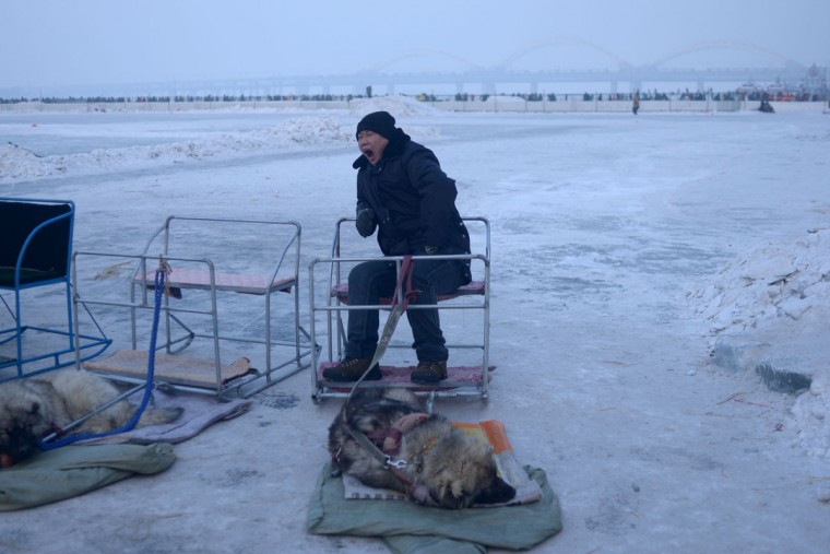A vendor yawns as he waits for the customers on the frozen Songhua river beside the Harbin international ice and snow festival in Harbin, northeast China's Heilongjiang province on January 3, 2016. (WANG ZHAO/AFP/Getty Images)