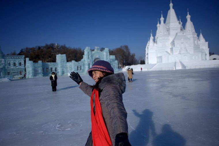 A woman poses for a picture in front of snow sculptures before the opening ceremony of the Harbin International Ice and Snow Festival in Harbin, northeast China's Heilongjiang province on January 4, 2016. (WANG ZHAO/AFP/Getty Images)