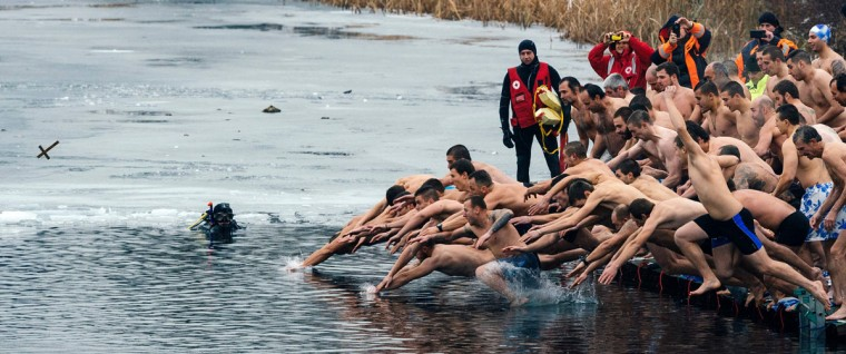 Bulgarians plunge into the icy winter water of a lake in Sofia, to catch a cross during the Epiphany Day celebrations on January 6, 2016. As a tradition, an Eastern Orthodox priest throws a cross in the river and it is believed that the one who retrieves it will be healthy through the year as well as all those who dance in the icy water. (AFP Photo / Dimitar Dilkoff)