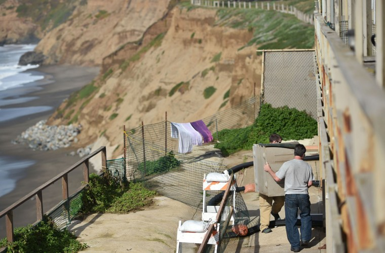 Residents are seen evacuating their apartments due to an eroding cliff in Pacifica, California on January 26, 2016. Storms and powerful waves caused by El Nino have been intensifying erosion along nearby coastal bluffs and beaches in the area. (JOSH EDELSON/AFP/Getty Images)