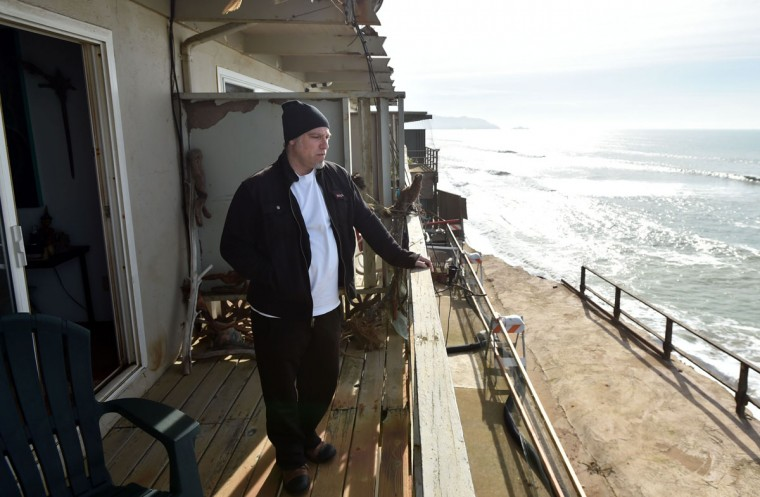 Resident Jonathan Levin surveys missing land from his balcony while residents evacuate in Pacifica, California on January 26, 2016. Storms and powerful waves caused by El Nino have been intensifying erosion along nearby coastal bluffs and beaches in the area. (JOSH EDELSON/AFP/Getty Images)