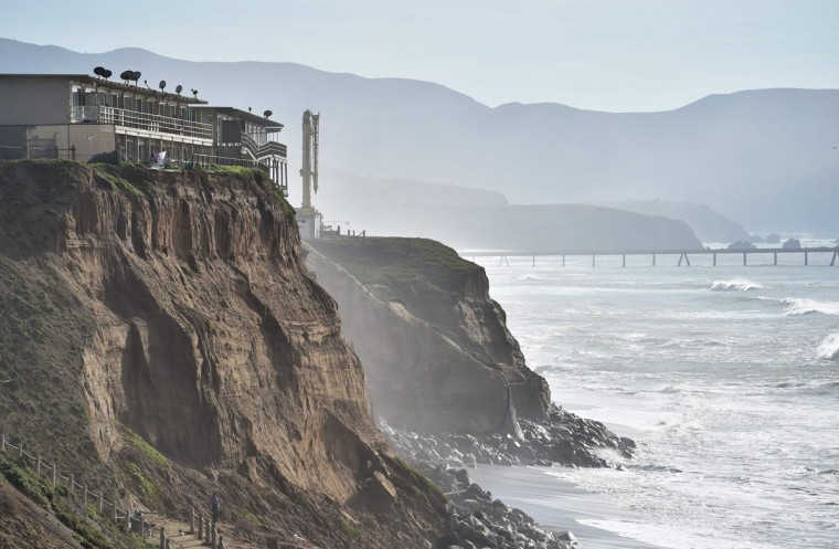 Apartments are seen at the edge of an eroding cliff while residents evacuate in Pacifica, California on January 26, 2016. Storms and powerful waves caused by El Nino have been intensifying erosion along nearby coastal bluffs and beaches in the area. (JOSH EDELSON/AFP/Getty Images)