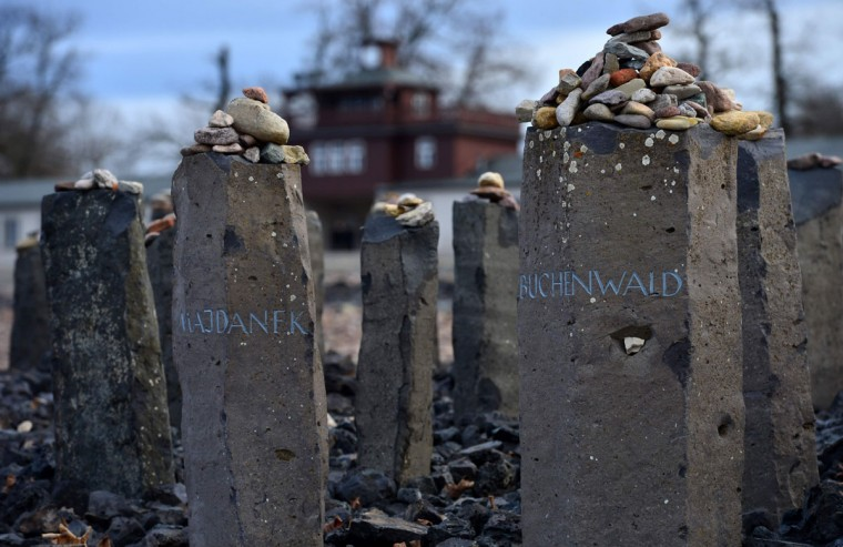 Stones lay on steles marked with the names of the former Nazi concentration camps Majdanek (L) and Buchenwald at the roll call ground of the former Buchenwald concentration camp near Weimar, central Germany, on January 27, 2016. At the occasion of the International Holocaust Remembrance Day, survivors of the Buchenwald camp and representatives of the regional government came together to lay a wreath. (AFP / Martin Schutt)