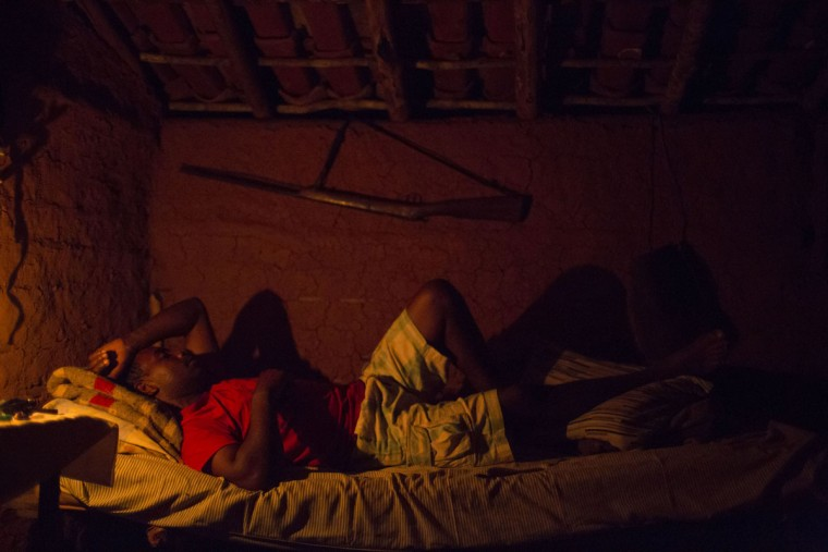 In this Nov. 15, 2015 photo, Jose Vanderson rests on his bed in Areinha, Minas Gerais state, Brazil. Born and raised in Areinha, Vanderson says diamond mining is part of the culture of this region, where the first stone was found nearly 300 years ago. (AP Photo/Felipe Dana)