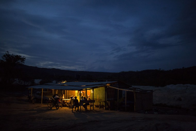 In this Nov. 17, 2015 photo, artisanal diamond miners gather inside a bar kept lit at dusk by a generator in Areinha, Minas Gerais state, Brazil. The rural miners live in wooden huts without electricity and bathe with water in buckets, barely surviving without a stable income but on rare occasions enjoying a windfall of tens of thousands of dollars. (AP Photo/Felipe Dana)