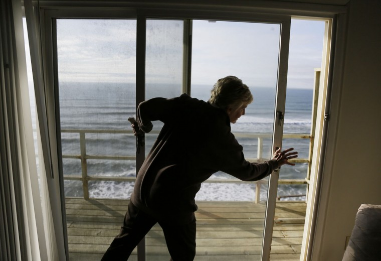 Eileen Horan shuts the door to her patio overlooking the Pacific Ocean after being forced to evacuate her apartment Monday, Jan. 25, 2016, in Pacifica, Calif. El Nino storms delivering crashing waves and powerful rain storms have put homes perched atop coastal bluffs near San Francisco in danger, forcing residents of an apartment complex on Monday to leave. (AP Photo/Eric Risberg)