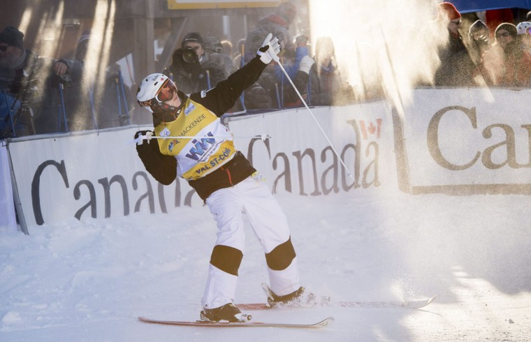 Men's moguls winner Canada's Mikael Kingsbury celebrates after crossing the finish line in the super final at the FIS Freestyle Ski World Cup on Saturday, Jan. 23, 2016, in Val Saint-Come, Canada. (Paul Chiasson/The Canadian Press via AP)