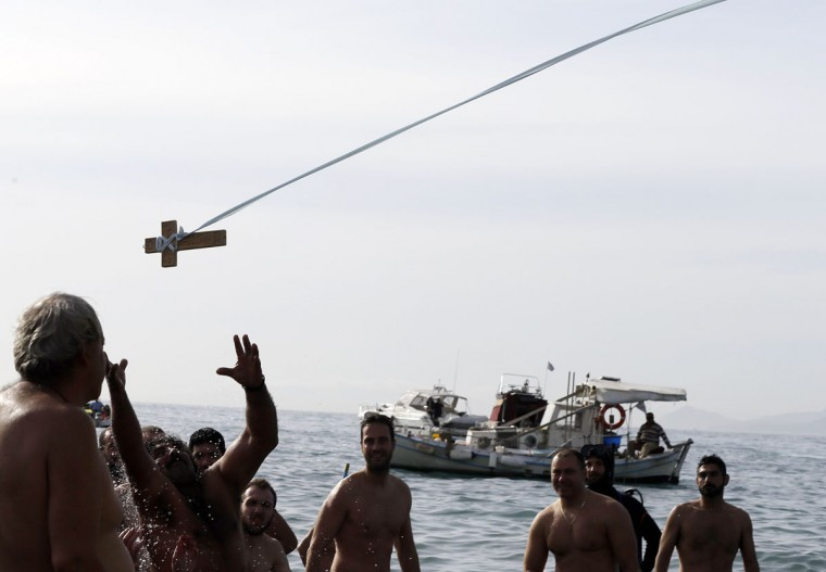 Pilgrims try to retrieve a wooden cross during an Epiphany ceremony to bless the water at the Athens' southern suburb of Paleo Faliro on Wednesday, Jan. 6, 2016. Similar ceremonies to mark Epiphany Day were held across Greece at the sea, rivers, lakes and dams. An Orthodox priest throws a cross into the water and the swimmers race to retrieve it first. (AP Photo/Thanassis Stavrakis)