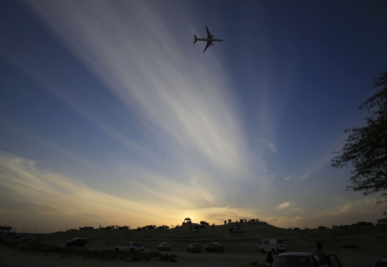Spectators watch from desert hills as the sun sets and an aircraft passes overhead during the Bahrain International Airshow in Sakhir, Bahrain, Friday, Jan. 22, 2016. (AP Photo/Hasan Jamali)