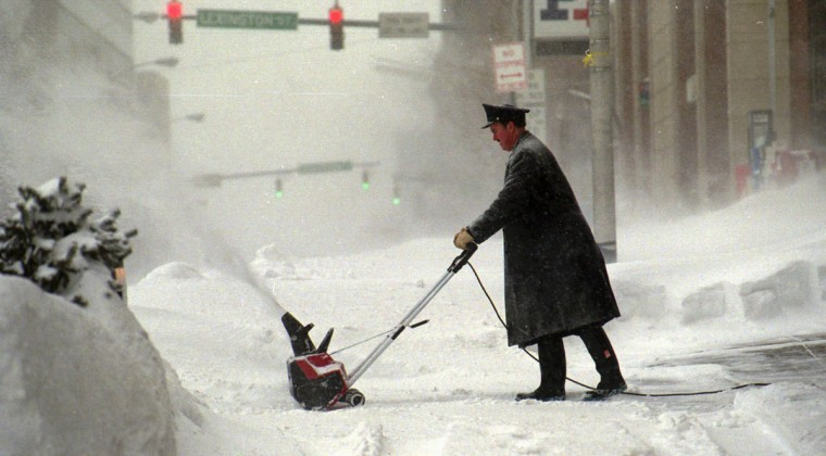Don Hamilton, the Doorman at the Tremont Plaza Hotel on St. Paul St., clears the sidewalk with a snow blower. (Algerina Perna/Baltimore Sun)
