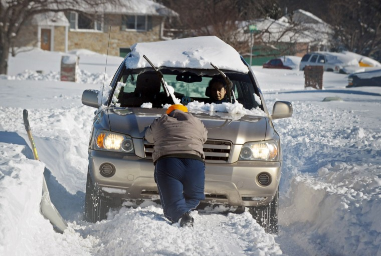 Beljinber Singh, center, pushes his stuck car with his wife Varinder Kaur at the wheel. Singh tries to get his car out of an unplowed road onto Mountain Road, which has been plowed, so he can go to work. Winter storm Jonas dumped over 29 inches of snow in the Baltimore area. (Kenneth K. Lam / Baltimore Sun)