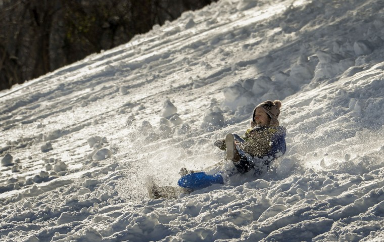 Amanda Ackerman and her three-year-old son, Michael Berardi slide down the steep hill at the Grand Pointe apartment complex in the Columbia village of Oakland Mills on Monday afternoon. They join many others enjoying the snow there in the wake of the Blizzard of 2016. (Doug Kapustin / Baltimore Sun Media Group)